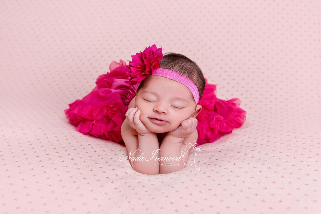 bebe tiens sur ses mains dans un tutu rose