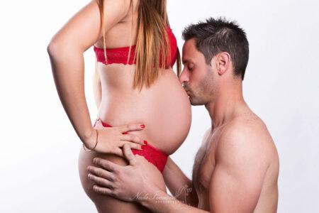 photographe beziers grossesse maman en rouge et papa qui fait un bisou sur le ventre