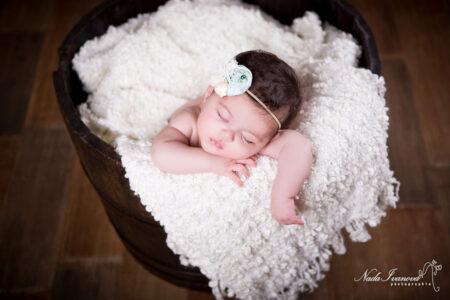 photographe clermont l herault bebe dans un seau en bois avec une fleur pale