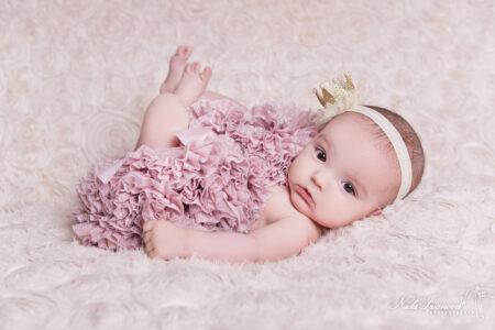 photographe clermont l herault nouveau ne sur fond rose pale avec les yeaux ouvert et une fleur dans les cheveux
