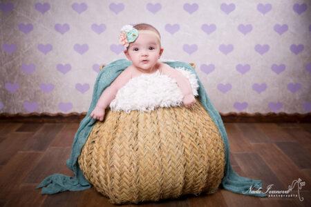 photographe marseillant bebe dans un pannier en fibre avec des coeur violet en fond