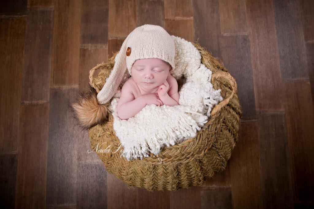 bébé dans un pannier vegetal et bonnet beige