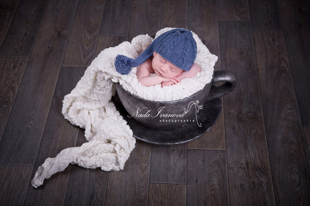 bébé dans une tasse argenté avec bonnet bleu
