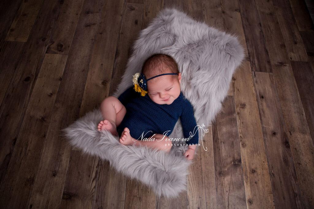 bebe avec body bleu sur fourure grise