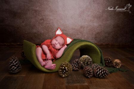 bebe avec bonnet renard sur faux gazon