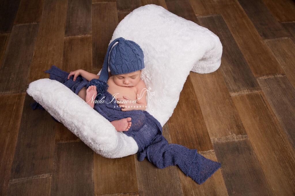 bebe qui dort avec un bonnet en laine bleu
