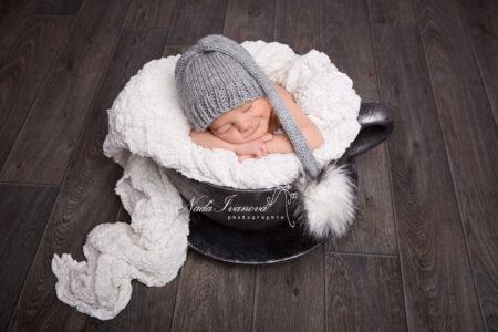 bebe qui dort en souriant dans une tasse argenté