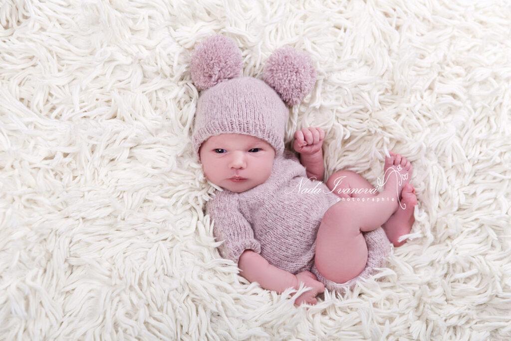 photographe agde bebe sur le dos avec pompon rose