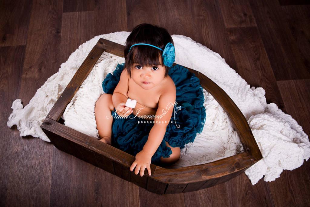 photo bébé dans un bateau en bois