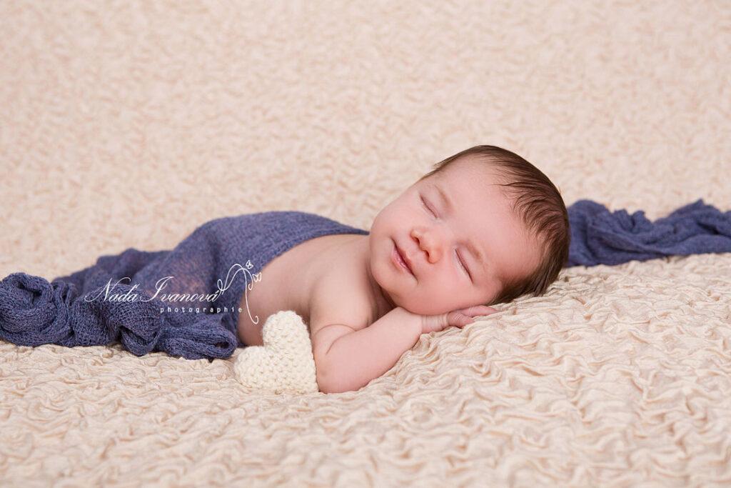 photo bebe sur fond beige et tissu bleu