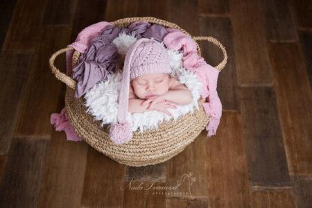 photographe nana ivanova bebe de clermont herault sur fond beige dans un pannier avec wrap rose